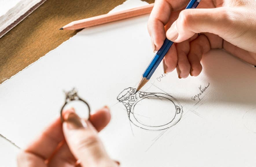 Left hand holding engagement ring and right hand sketching the design