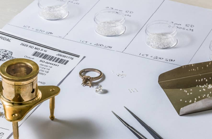 Engagement ring on a desk with a small diamond ready to be set