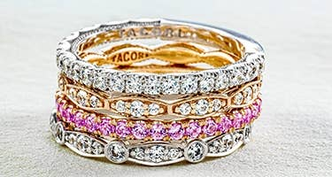 A stack of 4 Tacori rings featuring diamonds and pink sapphires with gold and platinum bands