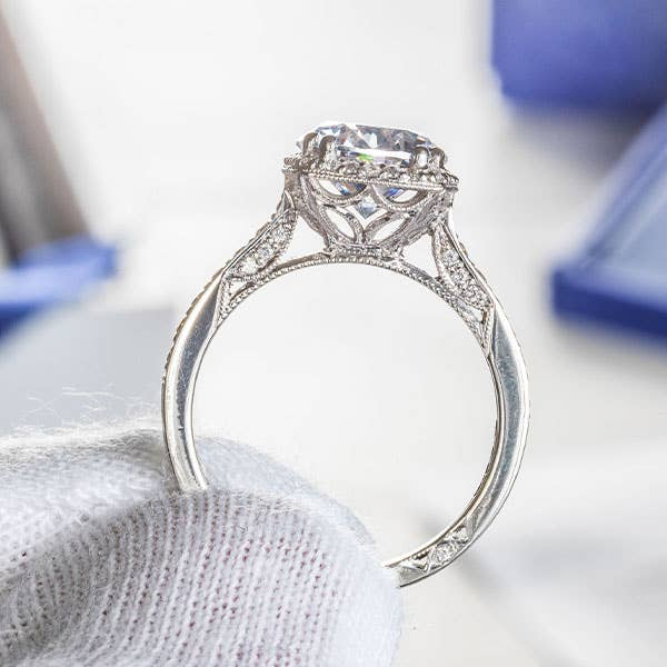 White gloved hand holding a Tacori engagement ring in close-up
