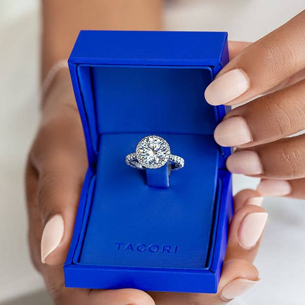 Hands holding a blue Tacori box open with ring inside